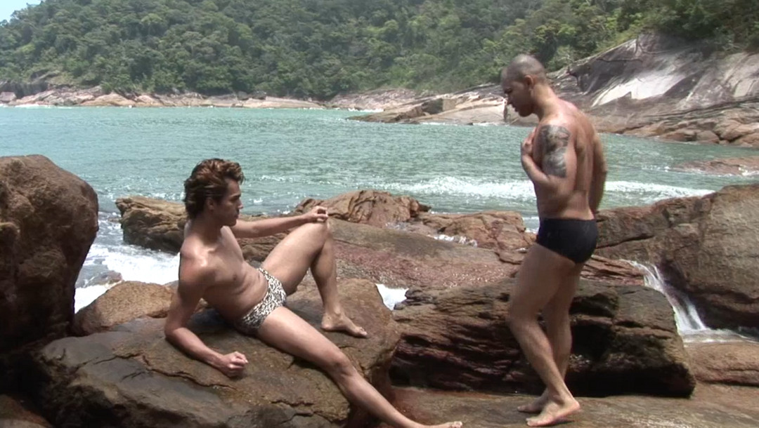 Two handsome, muscular Latino guys fuck behind a rock on the beach...