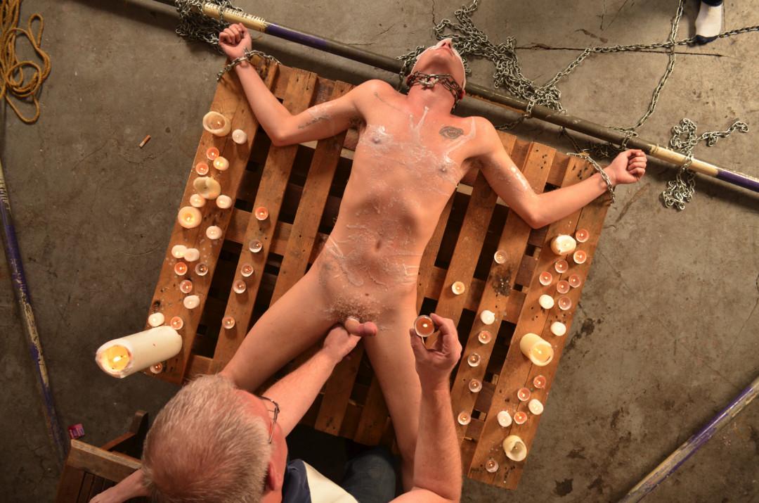 Jeune esclave gay en transe avec la cire de bougie