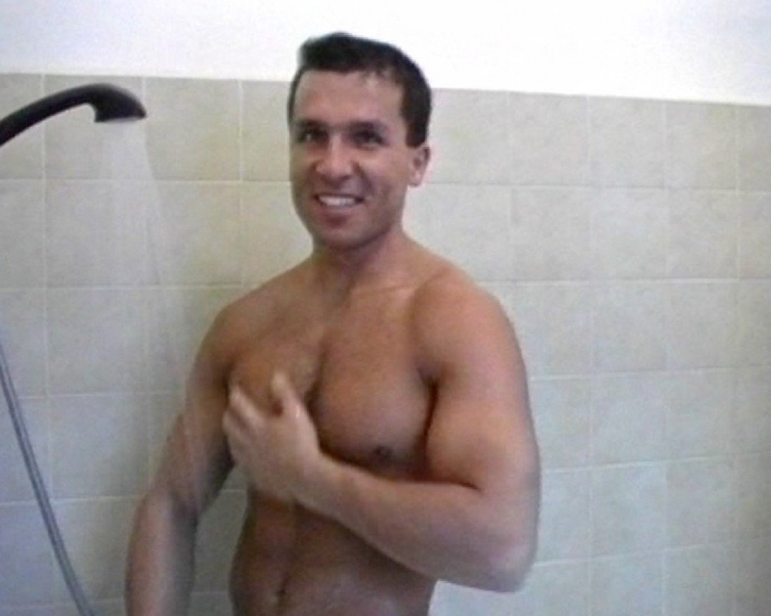 Muscled guy under shower